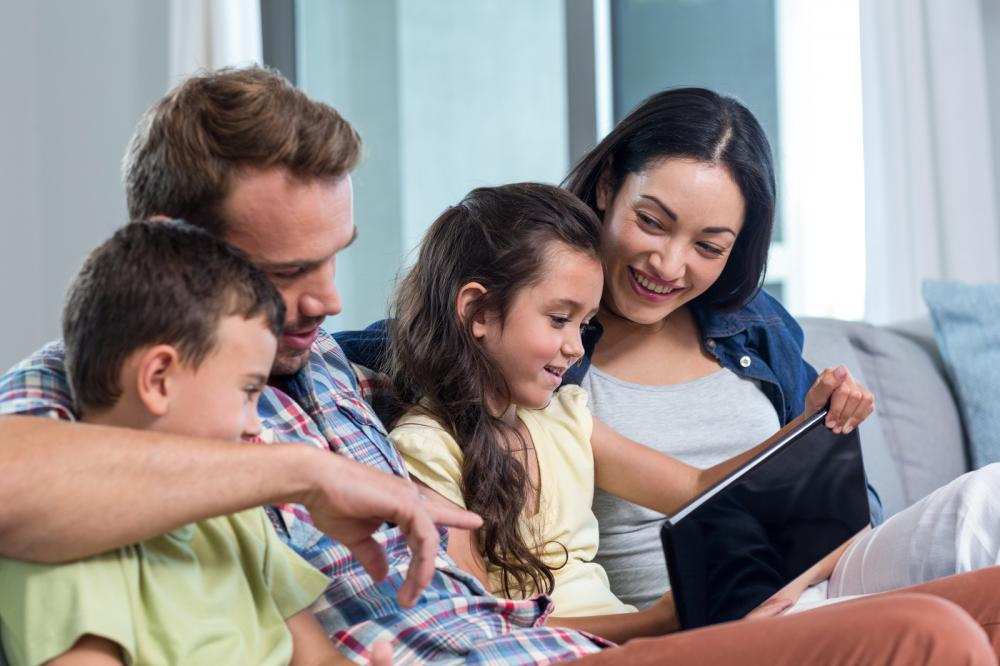 parents-sitting-with-son-and-daughter-and-looking-at-digital-tablet